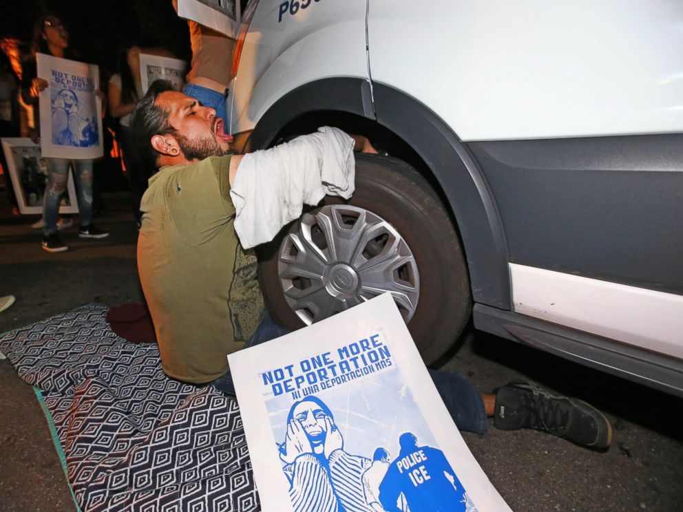 PHOTO: A protester locks himself to the van carrying Guadalupe Garcia de Rayos outside the ICE office in Phoenix, Ariz., Feb. 8, 2017.
