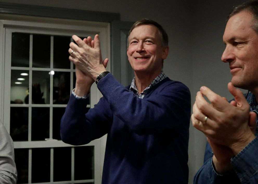 PHOTO:Former Colorado Gov. John Hickenlooper, left, applauds at a campaign house party, Feb. 13, 2019, in Manchester, N.H.