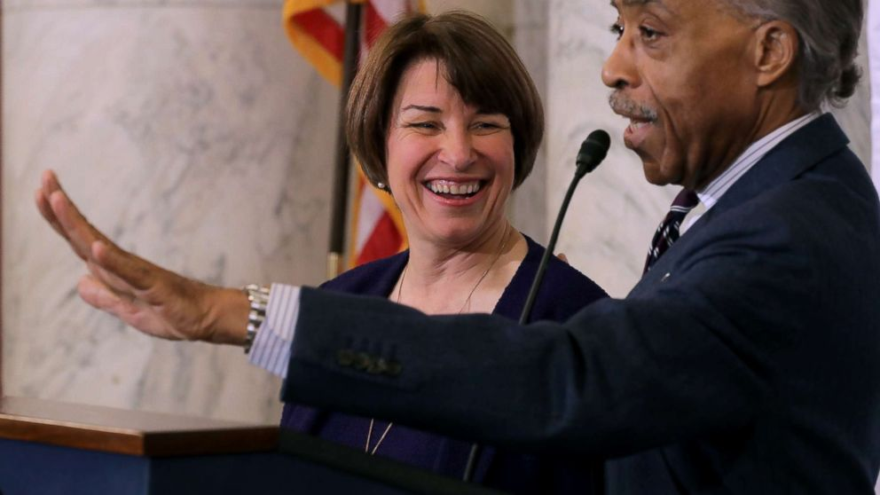 The Rev. Al Sharpton welcomes Sen. Amy Klobuchar (D-MN) to the podium before she addresses a post-midterm election meeting of Sharpton's National Action Network on Capitol Hill, Nov. 13, 2018.