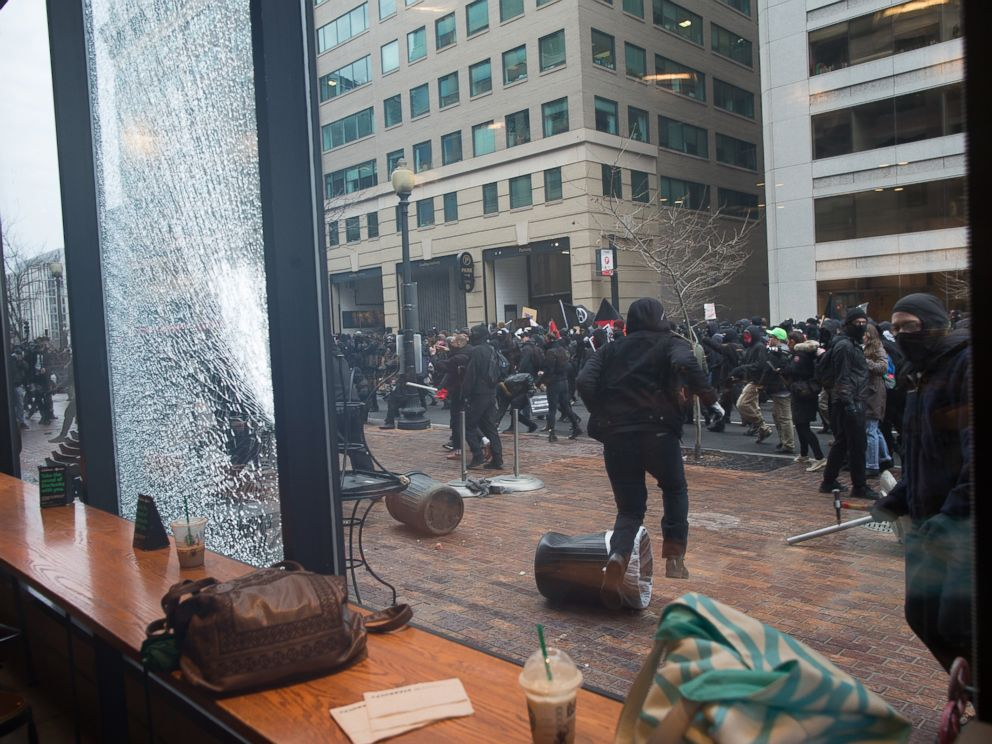 PHOTO: Anti Trump protestors hurled rocks and other debris at the Starbucks Cafe window as they ran through the streets, on Jan. 20, 2017, in Washington.