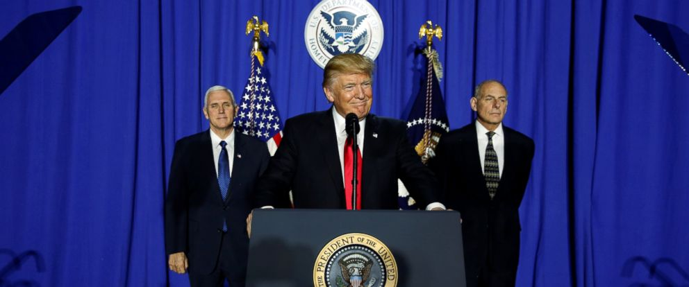 PHOTO: U.S. President Donald Trump (C), flanked by Vice President Mike Pence (L) and Homeland Security Secretary John Kelly (R), takes the stage to deliver remarks at Homeland Security headquarters in Washington, Jan. 25, 2017.