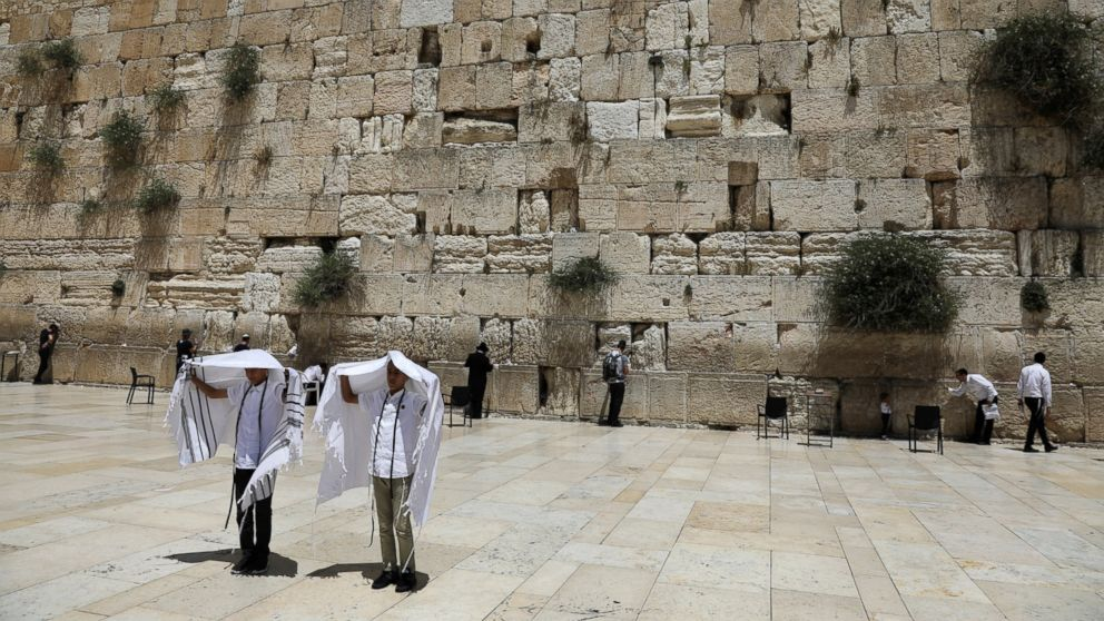 Youth hold their prayer shawls as they stand in front of the Western Wall, Judaism's holiest prayers site in Jerusalem's Old City, May 17, 2017. REUTERS/Ronen Zvulun