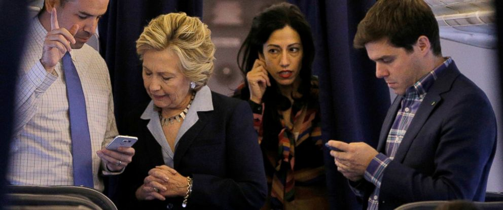 PHOTO: Democratic presidential nominee Hillary Clinton and national press secretary Brian Fallon (L) talk, with aide Huma Abedin (2nd R) and traveling press secretary Nick Merrill (R), onboard her campaign plane in White Plains, New York, Oct. 3, 2016.