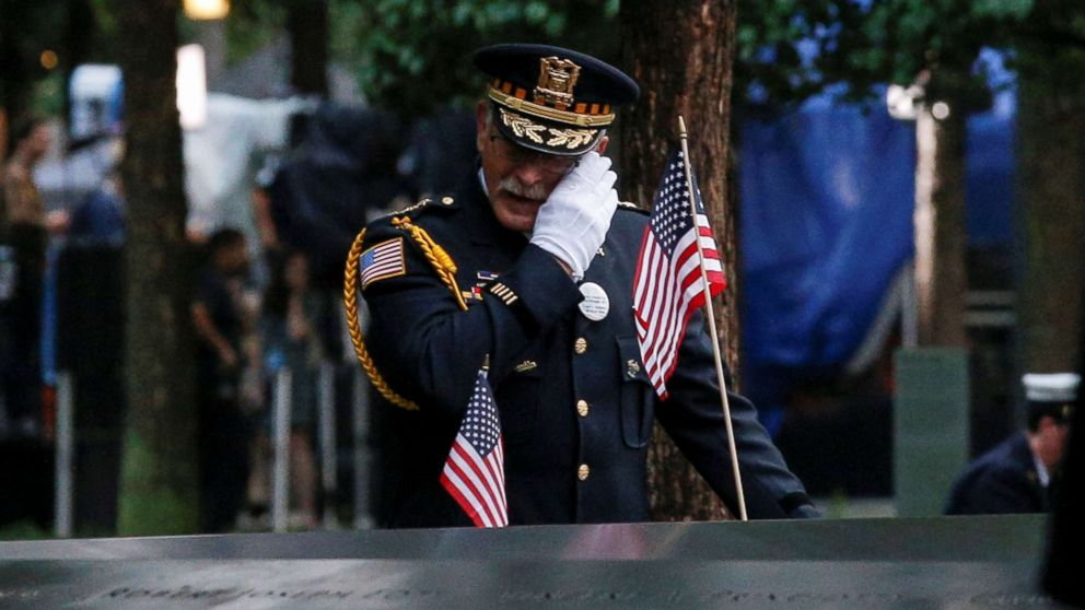A guest wipes a tear among names at the edge of the south reflecting pool at the National 9/11 Memorial and Museum during ceremonies marking the 17th anniversary of the Sept. 11, 2001 attacks on the World Trade Center in New York.