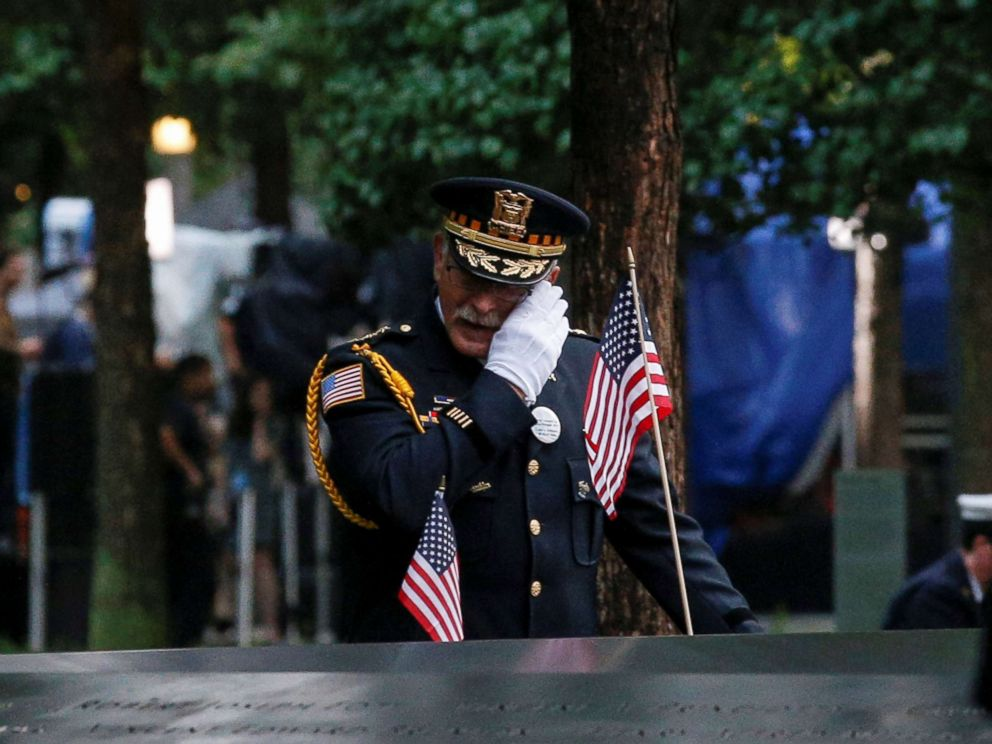 PHOTO: A guest wipes a tear among names at the edge of the south reflecting pool at the National 9/11 Memorial and Museum during ceremonies marking the 17th anniversary of the Sept. 11, 2001 attacks on the World Trade Center in New York.