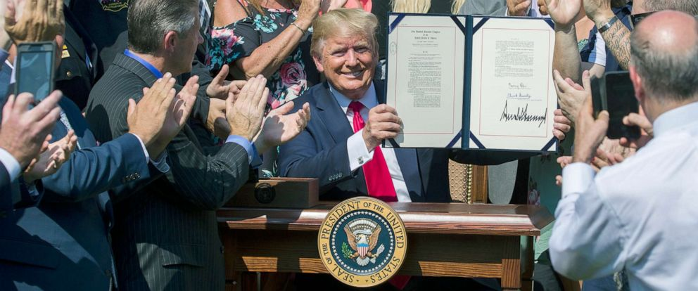 PHOTO:President Donald Trump holds up H.R. 1327, an act ensuring that a victims compensation fund related to the Sept. 11 attacks never runs out of money, after signing it in the Rose Garden of the White House, July 29, 2019.
