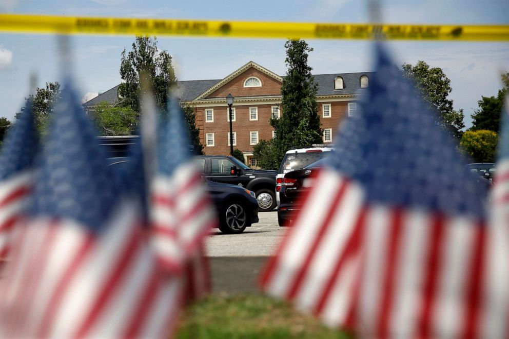 PHOTO: American flags that are part of a makeshift memorial stand at the edge of a police cordon in front of a municipal building that was the scene of a shooting, June 1, 2019, in Virginia Beach, Va.