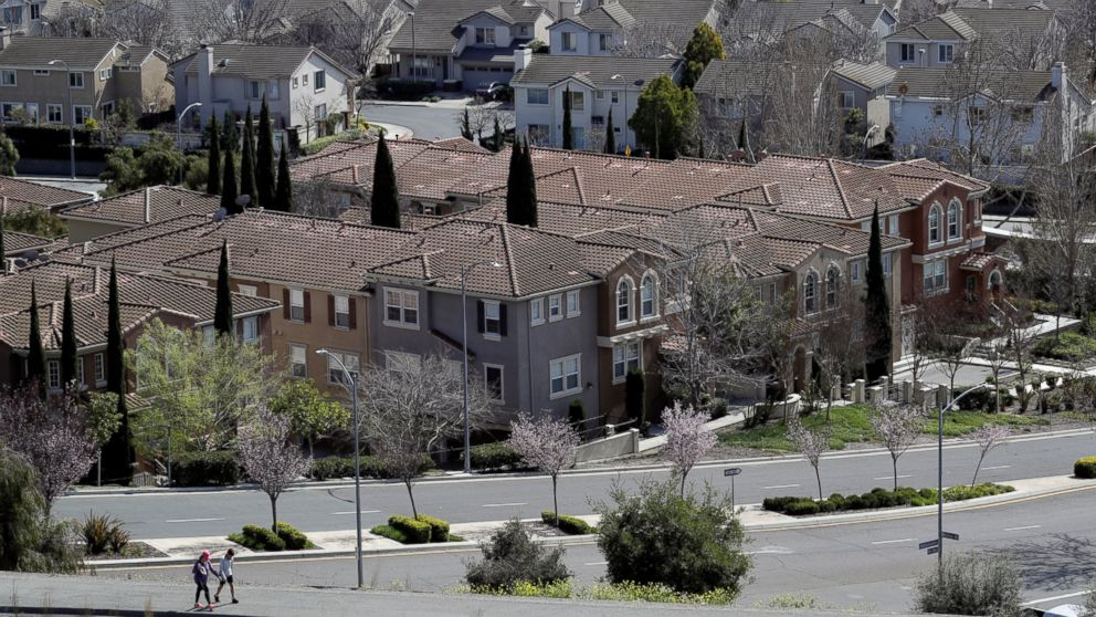 FILE - In this March 6, 2018, file photo, people walk along a path in front of a row of homes in San Jose, Calif. The suburbs are usually seen as the great political swing area in the United States, toggling back and forth between the two parties. But a new poll shows the suburbs are as polarized along partisan lines as the rest of the nation. (AP Photo/Marcio Jose Sanchez, File)