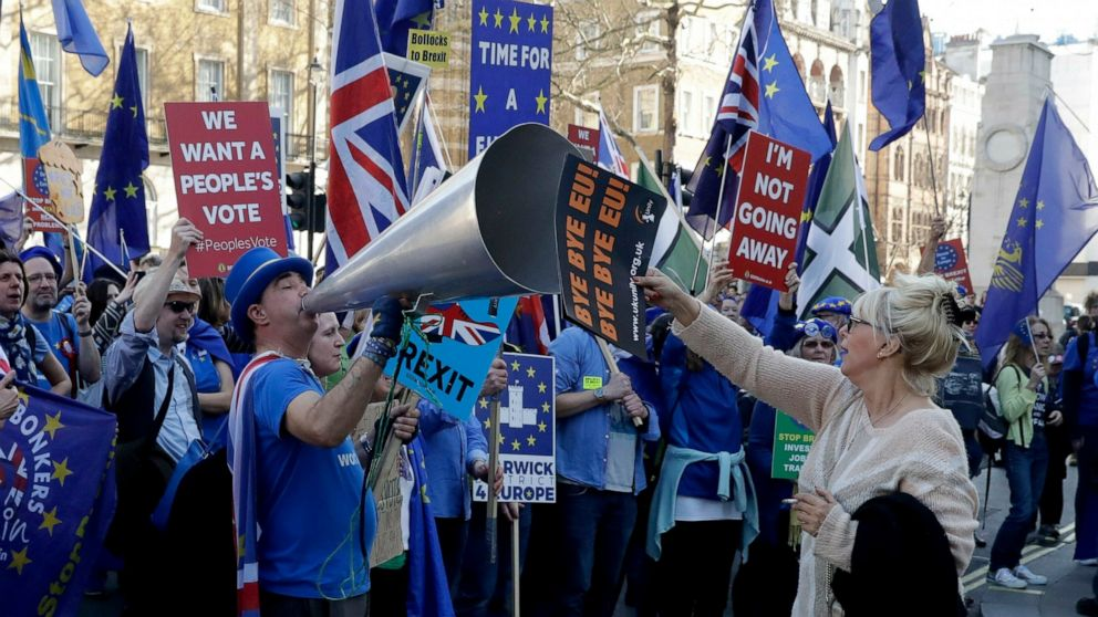 FILE - In this Wednesday, Feb. 27, 2019 file photo a leave the European Union (EU) supporter, at right, holds a placard up in front of remain in the EU supporters protesting outside Downing Street in London. (AP Photo/Matt Dunham, File)