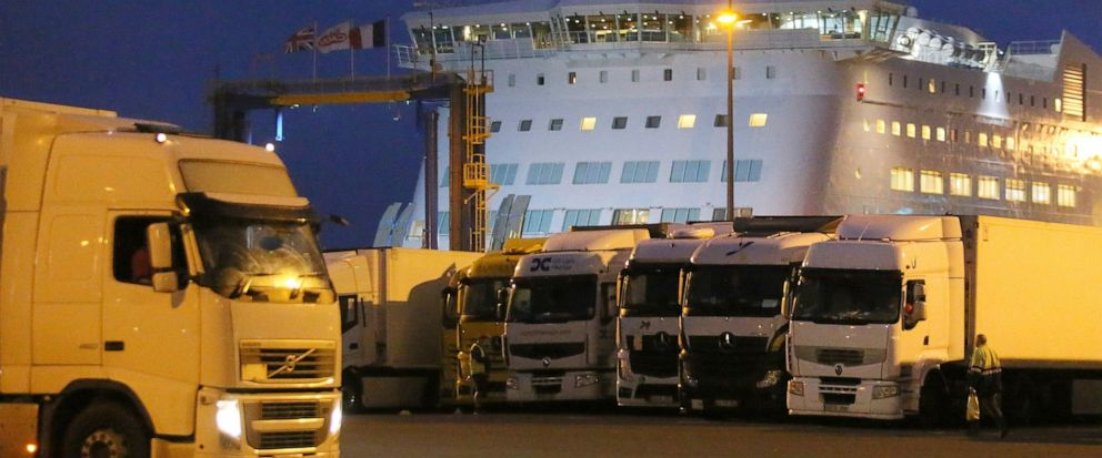 Trucks park as a ferry coming from Britains port of Portsmouth docks at the transit zone at the port of Ouistreham, Normandy, Thursday, Sept.12, 2019. France has trained 600 new customs officers and built extra parking lots arounds its ports to hold