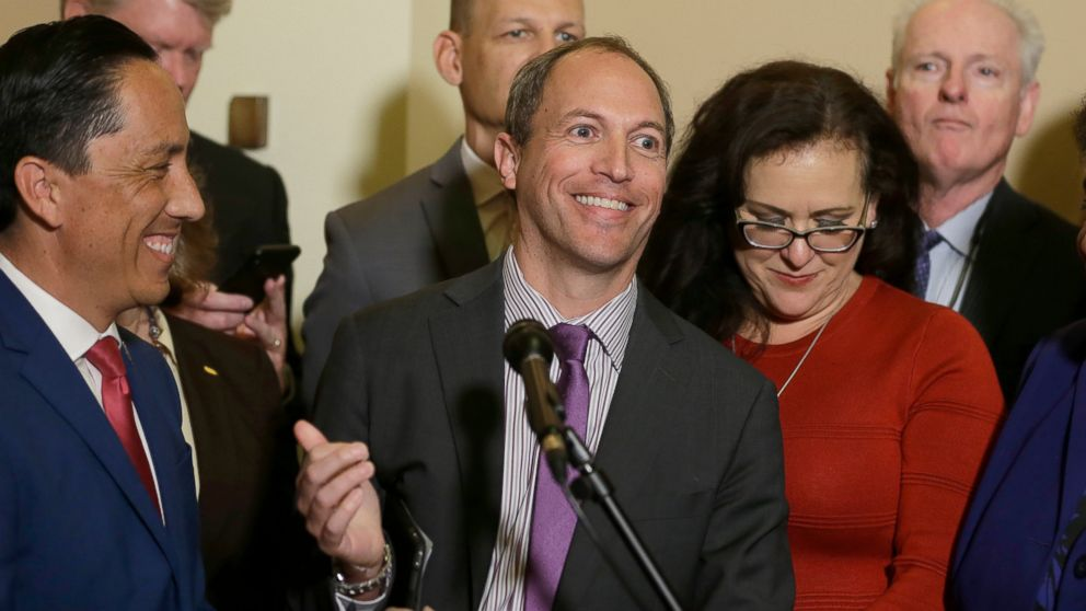 Assemblyman Brian Maienschein, center, smiles at a news conference where he announced he was switching party registration from Republican to Democrat, Thursday, Jan. 24, 2019, in Sacramento, Calif. Maienschein was flanked by Democratic Assembly members, from left, including Todd Gloria of San Diego, Mark Stone of Scotts Valley, Kevin McCarty of Sacramento, Lorena Gonzalez Fletcher of San Diego and Tom Daly of Anaheim. (AP Photo/Rich Pedroncelli)
