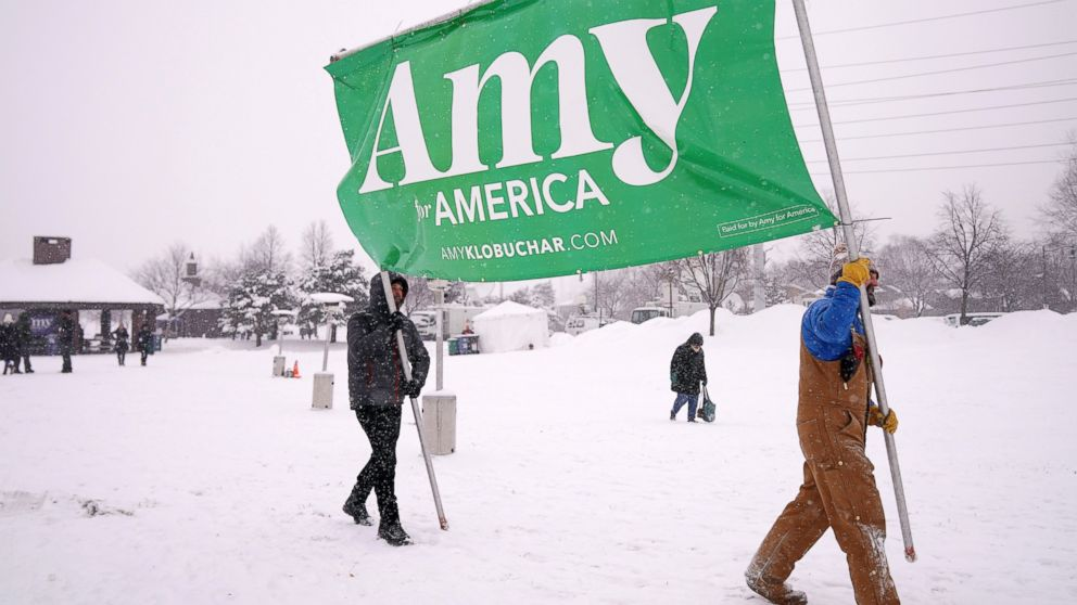 "Volunteers Tim Schumann, left, and Chase Cushman move an ""Amy for America"" sign into place Sunday, Feb. 10, 2019, prior to Democratic Sen. Amy Klobuchar's announcement of her decision in the race for president at a rally in Minneapolis. (Anthony Souffle/Star Tribune via AP)"