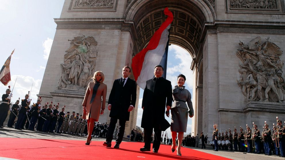 French President Emmanuel Macron, 2nd left, his wife Brigitte Marcon, left, Chinese President President Xi Jinping and his wife Peng Liyuan leave the Arc de Triomphe monument after attending a wreath laying ceremony at the Tomb of the Unknown soldier, in Paris, France, Monday, March 25, 2019. Chinese President Xi Jinping is on a 3-day state visit in France where he is expected to sign a series of bilateral and economic deals on energy, the food industry, transport and other sectors. (AP Photo/Francois Mori, Pool)