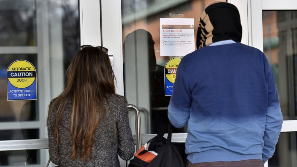 """December 22, 2018 Atlanta - Visitors read an """"Area Closed"""" sign due to a government shutdown at the Martin Luther King Jr. National Historical Park Visitor Center on Saturday, December 22, 2018. The third shutdown in less than a year could mean a tough holiday season for thousands of federal workers in Georgia and sow uncertainty for countless more who rely on government services. (Hyosub Shin/Atlanta Journal-Constitution via AP)"""