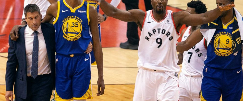 Golden State Warriors forward Kevin Durant (35) walks off the court after sustaining an injury as Toronto Raptors center Serge Ibaka (9) gestures to the crowd during first half basketball action in Game 5 of the NBA Finals in Toronto on Monday, June