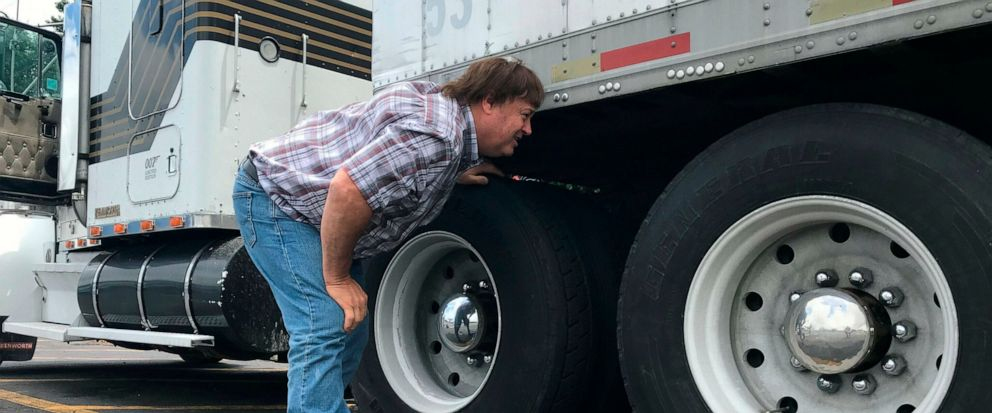 In this June 13, 2019 photo, truck driver Terry Button looks over his trailer during at stop in Opal, Va. The Trump administration has moved a step closer to relaxing federal regulations governing the amount of time truck drivers can spend behind the