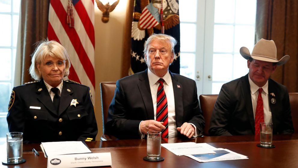"""President Donald Trump, with Carolyn """"Bunny"""" Welsh, sheriff of Chester County, Pa., left, and AJ Louderback, sheriff of Jackson County, Texas, attends a roundtable discussion on border security with local leaders, Friday Jan. 11, 2019, in the Cabinet Room of the White House in Washington. (AP Photo/Jacquelyn Martin)"""