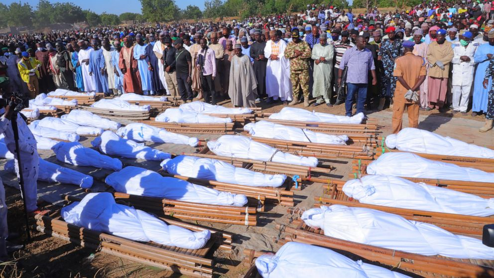 People attend a funeral for those killed by suspected Boko Haram militants in Zaabarmar, Nigeria, Sunday, Nov. 29, 2020. Nigerian officials say suspected members of the Islamic militant group Boko Haram have killed at least 40 rice farmers and fisher