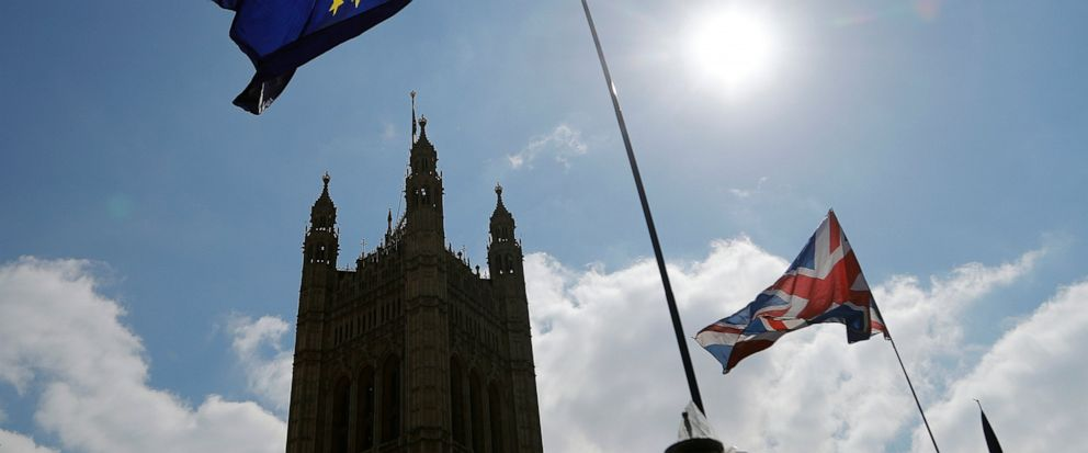 Protestor flags fly opposite the Houses of Parliament in London, Thursday, April 11, 2019. European Union leaders on Thursday offered Britain an extension to Brexit that would allow the country to delay its EU departure date until Oct. 31. (AP Photo/