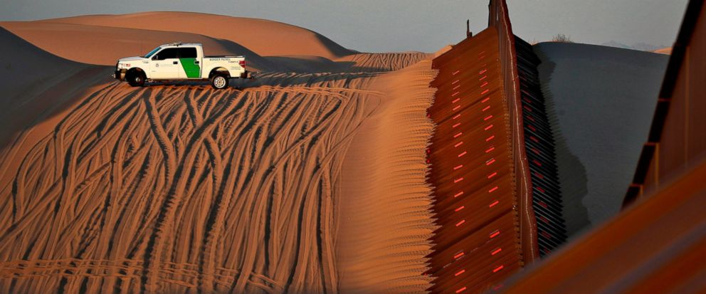 FILE - In this July 18, 2018 file photo, a U.S. Customs and Border Patrol agent patrols a section of floating fence at sunset that runs through Imperial Sand Dunes along the international border with Mexico in Imperial County, Calif. President Donald