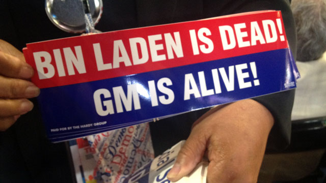 """PHOTO: Delegate holds up a """"Bin Laden Is Dead! GM Is Alive!"""" bumper sticker at the Democratic National Convention."""
