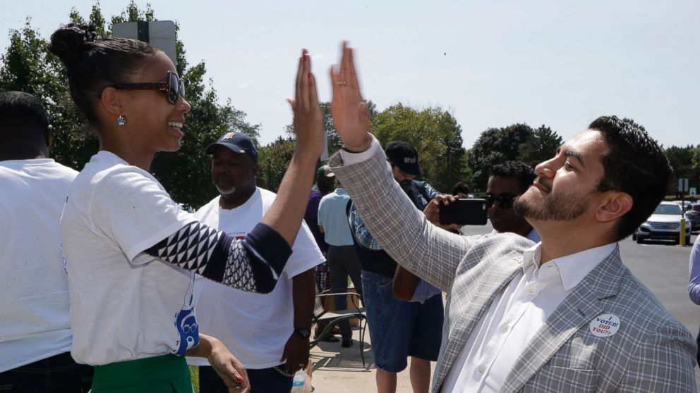 Dr. Abdul El-Sayed high-fives supporter Sonique Watson in Detroit, Aug. 8, 2017.