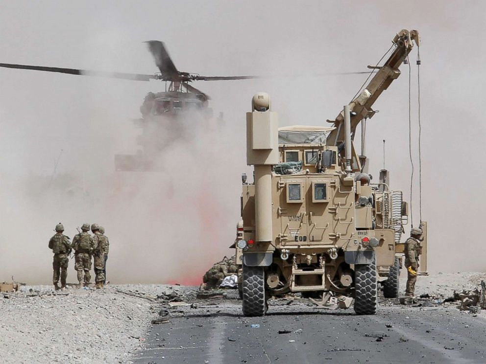 PHOTO: U.S. troops assess the damage to an armored vehicle of the NATO-led military coalition after a suicide attack in Kandahar province, Afghanistan, Aug. 2, 2017.