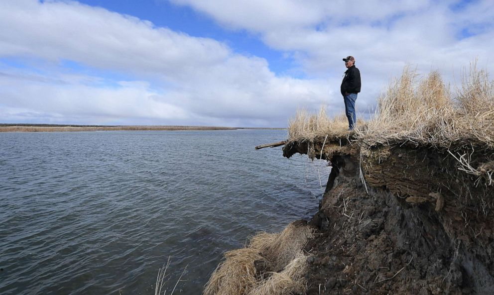 PHOTO: Tribal elder Warren Jones stands on the edge of climate change erosion caused by melting permafrost tundra and the disappearance of sea ice which formed a protective barrier, on Yukon Delta in Alaska, April 12, 2019.