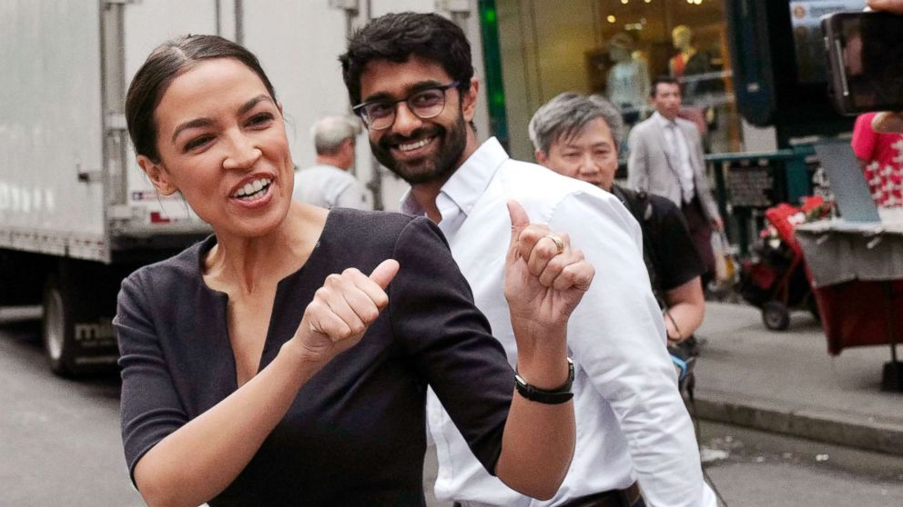Alexandria Ocasio-Cortez, the winner of a Democratic Congressional primary in New York, reacts to a passerby, June 27, 2018, in New York. Ocasio-Cortez, 28, upset U.S. Rep. Joe Crowley in Tuesday's election.