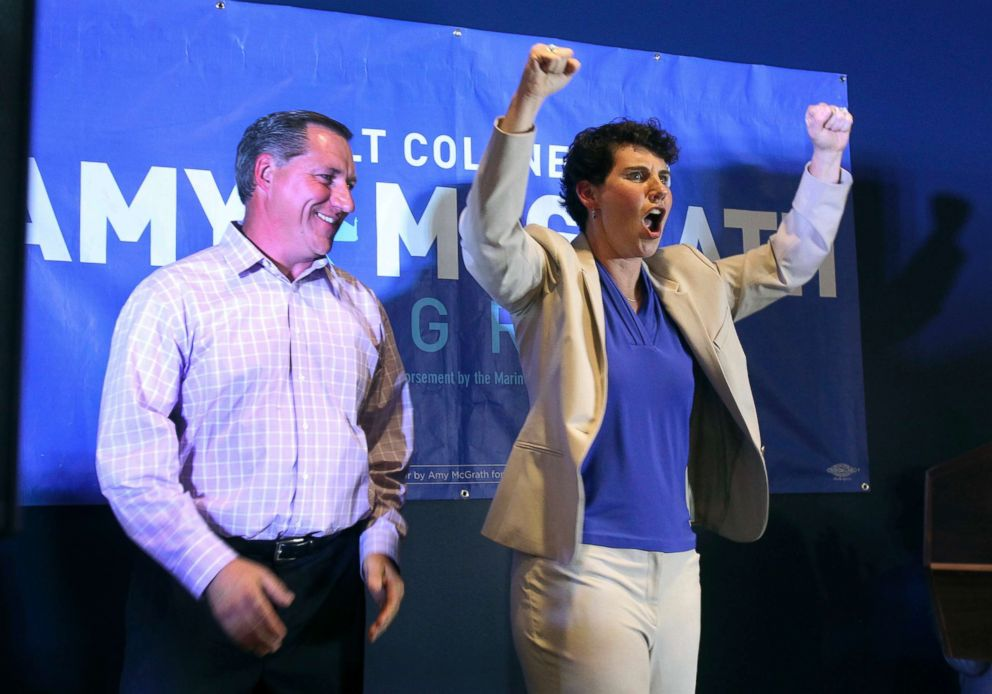 PHOTO: Amy McGrath, right, with her husband, Erik Henderson, pumps her fists after being elected as the Democratic candidate for Kentuckys 6th Congressional District, May 22, 2018, in Richmond, Ky.