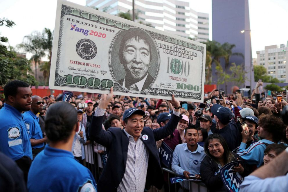 PHOTO: Democratic presidential candidate Andrew Yang hoists a supporters sign after speaking at a rally in downtown Los Angeles, April 22, 2019.