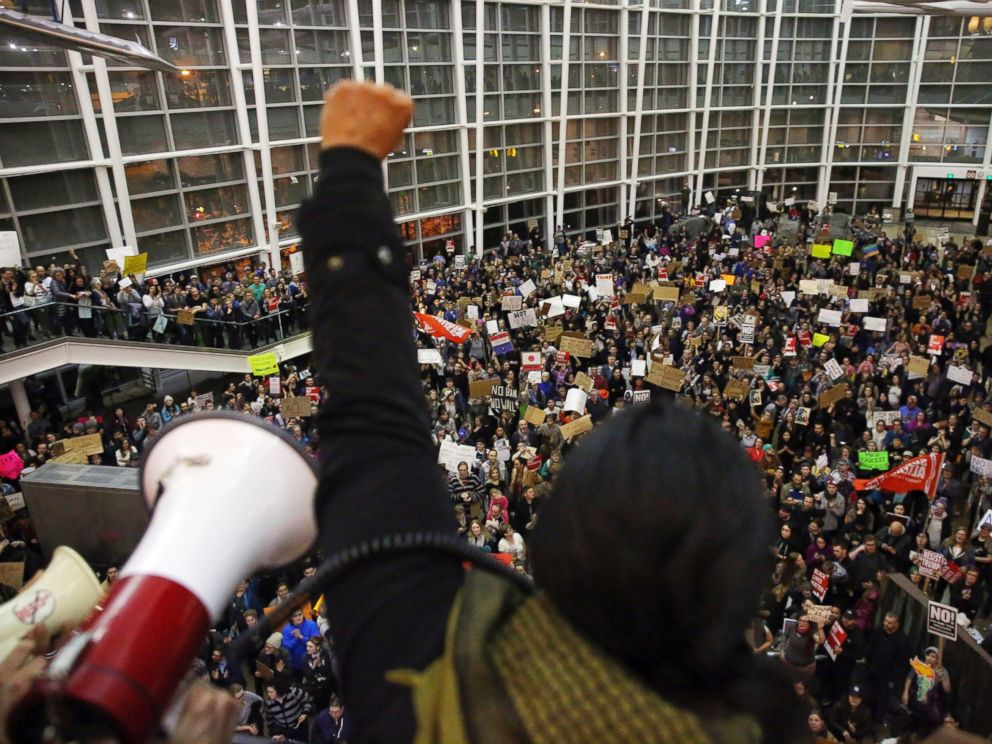 PHOTO: Seattle city councilwoman Kshama Sawant raises a fist over the crowd, as more than 1,000 people gather at Seattle-Tacoma International Airport, to protest President Donald Trumps order that restricts immigration to the U.S., Jan. 28, 2017.