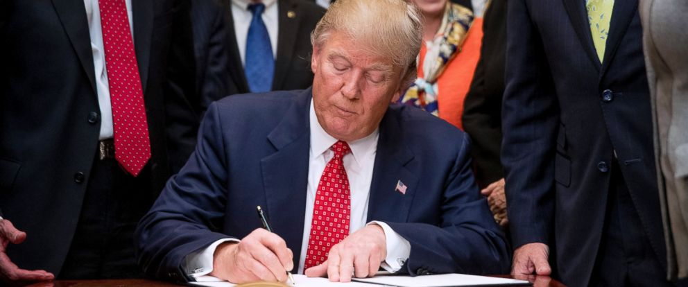 PHOTO: President Donald Trump signs the Waters of the United States (WOTUS) executive order, Feb. 28, 2017, in the Roosevelt Room in the White House in Washington, D.C.