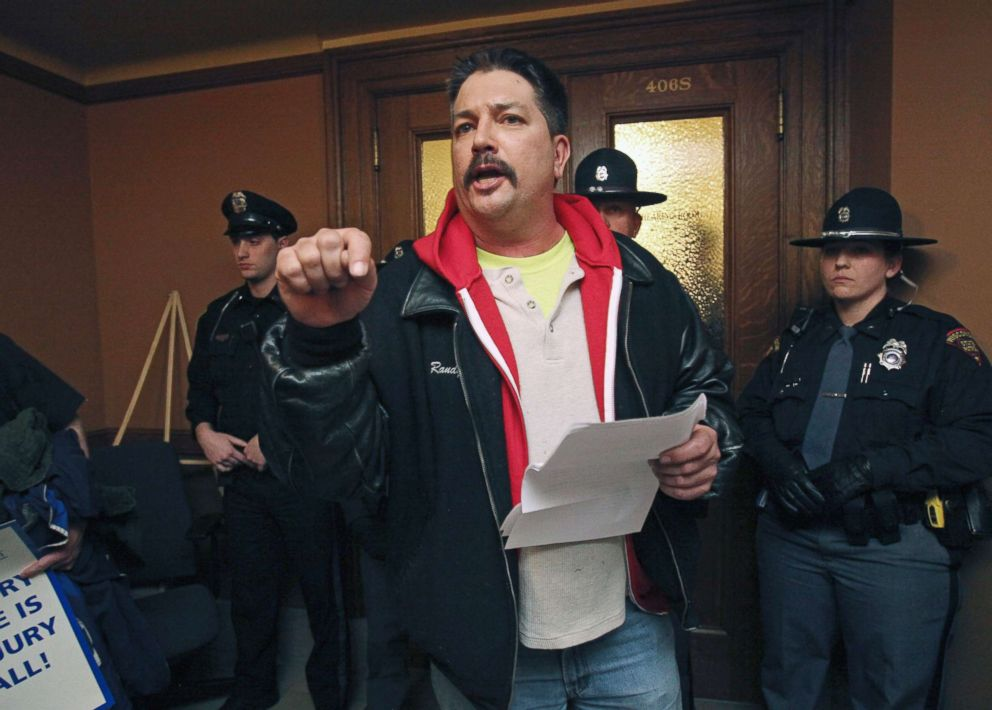 PHOTO: Randy Bryce, of Caledonia, Wis. reads his testimony outside a hearing room that is barricaded by police after he was not able to speak during a meeting for a right-to-work bill at the Wisconsin State Capitol in Madison, Wis., Feb. 24, 2015.