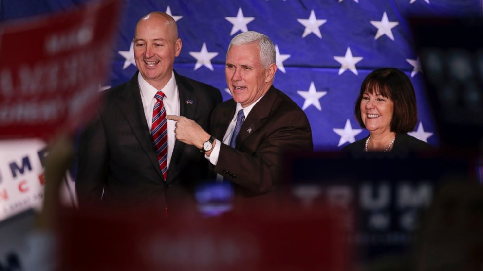 Mike Pence, and his wife Karen, stand on stage with Nebraska Governor Pete Ricketts before speaking at a campaign stop in Omaha, Oct. 27, 2016.