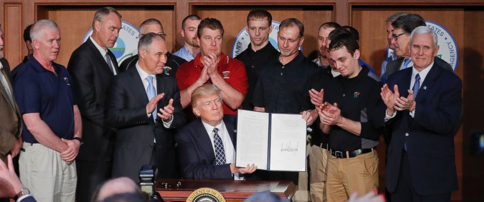 PHOTO: President Donald Trump, accompanied by Environmental Protection Agency (EPA) Administrator Scott Pruitt, third from left, applaud as he holds up the signed Energy Independence Executive Order, March 28, 2017, at EPA headquarters in Washington.