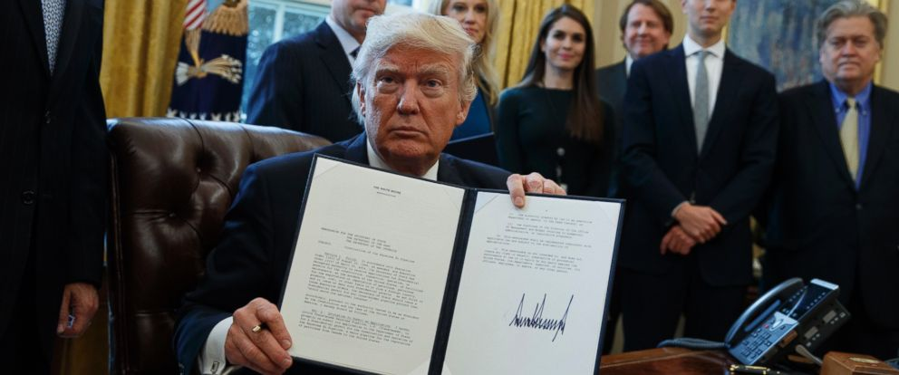 PHOTO: President Donald Trump shows his signature on an executive order on the Keystone XL pipeline, Jan. 24, 2017, in the Oval Office of the White House in Washington.