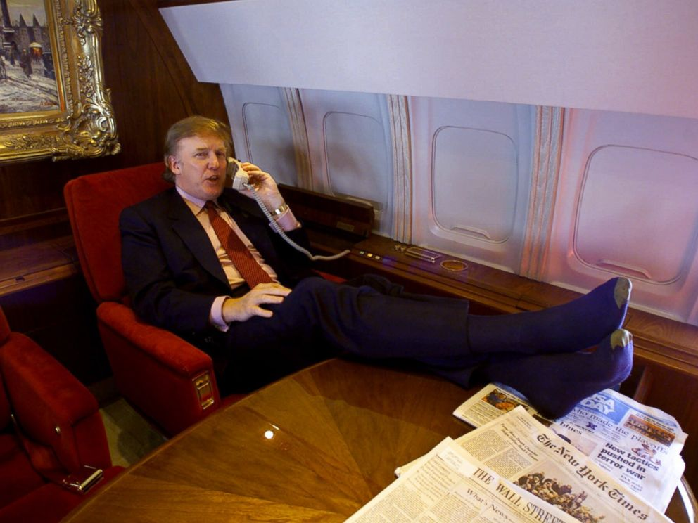 PHOTO: Donald Trump uses the phone and puts his sock-covered feet on the table in his private plane as he flies to Minnesota for a speech and to attend a fund-raiser for Gov. Jesse Ventura, Friday Jan. 7, 2000.