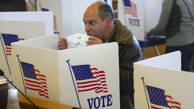 PHOTO:Seth Blank seals an envelope containing his absentee ballot for the Nov. 6th election at the town hall in Cape Elizabeth, Maine, Thursday, Oct. 25, 2012.