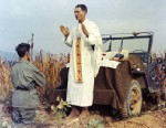 PHOTO: Father Emil Kapaun celebrates Mass using the hood of his jeep as an altar, as his assistant, Patrick J. Schuler, kneels in prayer in Korea on Oct. 7, 1950, less than a month before Kapaun was taken prisoner where he died in a prisoner of war camp o