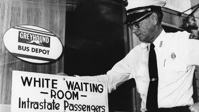 """PHOTO: Police Chief George H. Guy poses beside the """"White waiting room"""" sign posted outside the Greyhound bus terminal in McComb, Mi., on Nov. 2, 1961."""