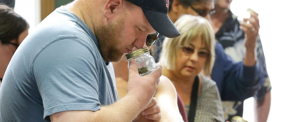 PHOTO: A customer sniffs a strain of recreational marijuana at Top Shelf Cannabis, Tuesday, July 8, 2014, in Bellingham, Wash., during the first half-hour of legal sales in the states.