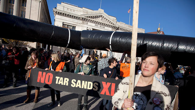 PHOTO: Demonstrators march with a replica of a pipeline during a protest to demand a stop to the Keystone XL tar sands oil pipeline outside the White House, in this Nov. 6, 2011 file photo, in Washington.
