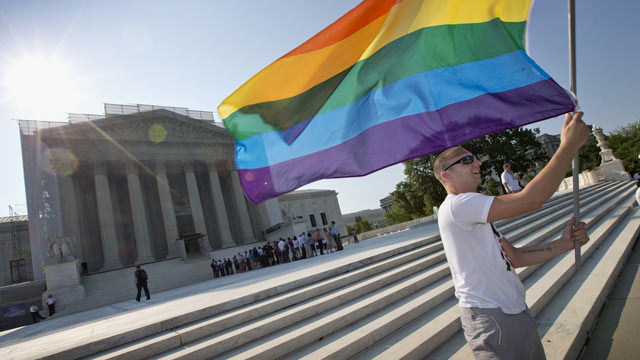 PHOTO: Vin Testa of Washington waves a rainbow flag in support of gay rights outside the Supreme Court in Washington, June 25, 2013, as key decisions are expected to be announced.