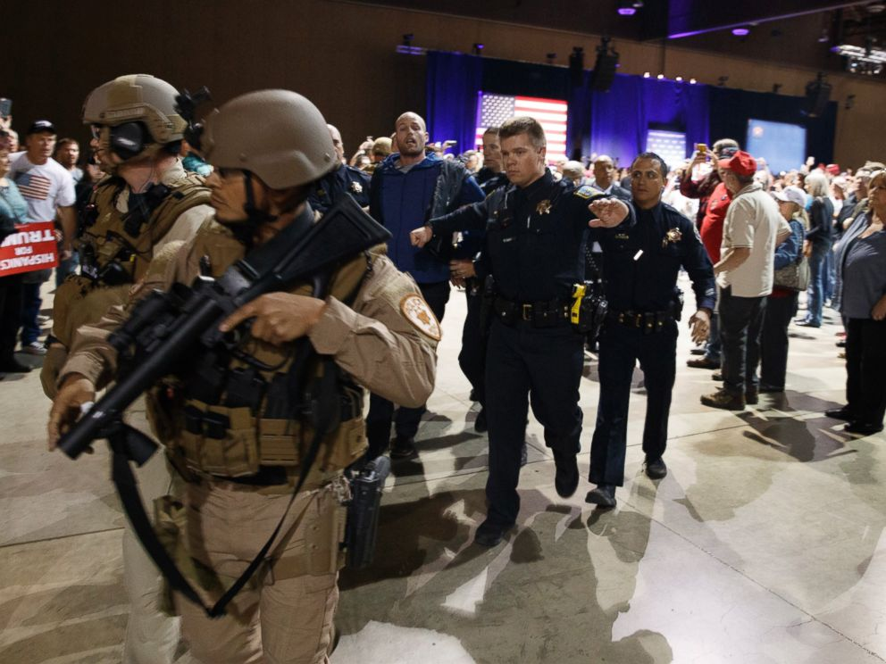 PHOTO: A man, at center with blue sweater, is escorted by law enforcement officers moments after Republican presidential candidate Donald Trump was rushed offstage by Secret Service agents during a campaign rally in Reno, Nev., on Saturday, Nov. 5, 2016.