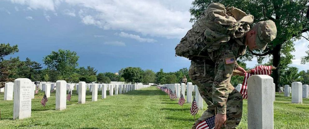 "PHOTO: A soldier from the U.S. Armys ""Old Guard,"" the 3rd U.S. Infantry Regiment, places American flags in front of more than 228,000 headstones in Arlington National Cemetery, May 23, 2019."