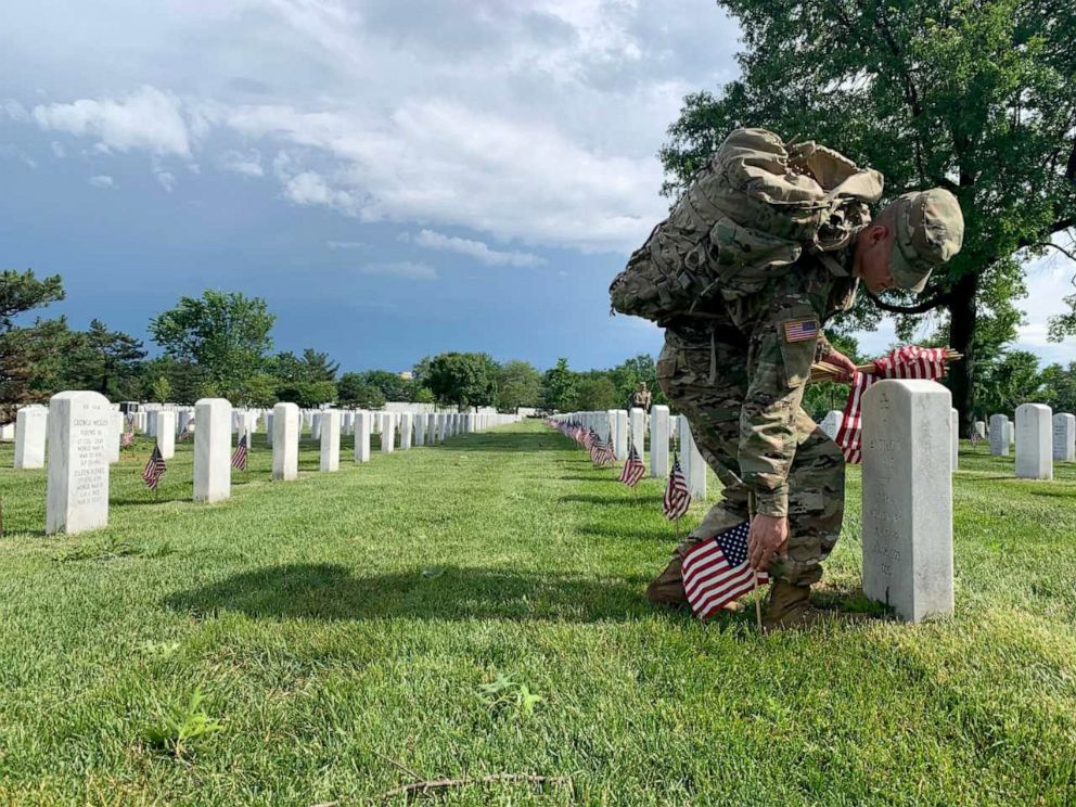 PHOTO: A soldier from the U.S. Armys Old Guard, the 3rd U.S. Infantry Regiment, places American flags in front of more than 228,000 headstones in Arlington National Cemetery, May 23, 2019.