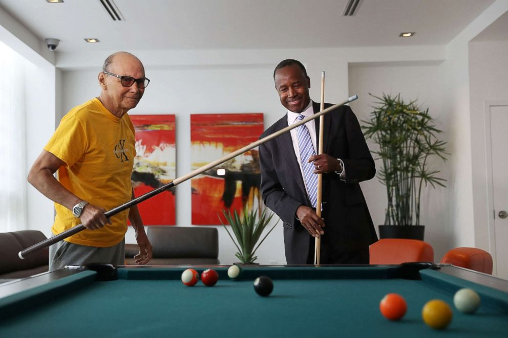 PHOTO: Housing and Urban Development Secretary Ben Carson plays pool with Armando de la Noval as he visits Colllins Park apartment complex on April 12, 2017 in Miami during a national listening tour.