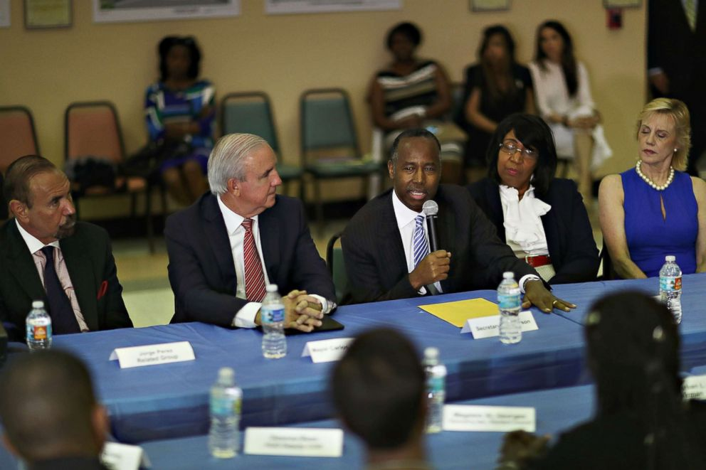 PHOTO: (L-R) Jorge Perez, CEO, Related Urban Group, Carlos Gimenez, mayor of Miami-Dade, listen as U.S. Housing and Urban Development Secretary Ben Carson speaks during a visit to the Liberty Square apartment complex on April 12, 2017 in Miami.