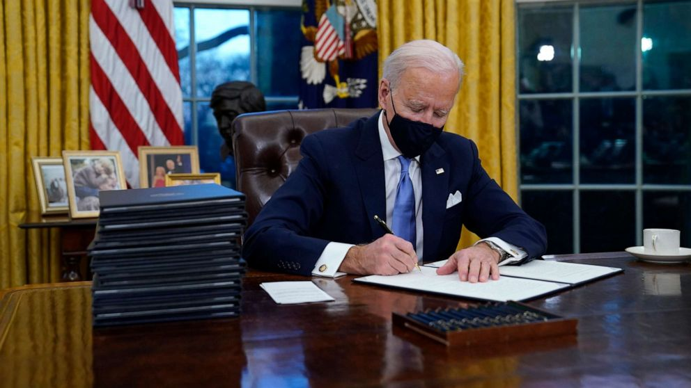 PHOTO: President Joe Biden signs his first executive order in the Oval Office of the White House, Jan. 20, 2021, in Washington.